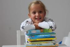 Een meisje met een grote stapel boeken