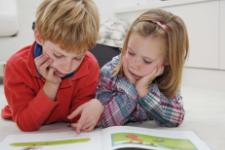 Twee jonge kinderen lezen samen een boek